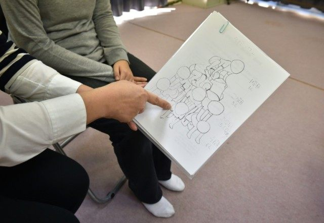 "The mother of a student at a Tokyo primary school, and who would only be identified by the initial M, shows an illustration of ""Kumitaiso"" or a gymnastic formation and her daughter's position when an accident occurred"
