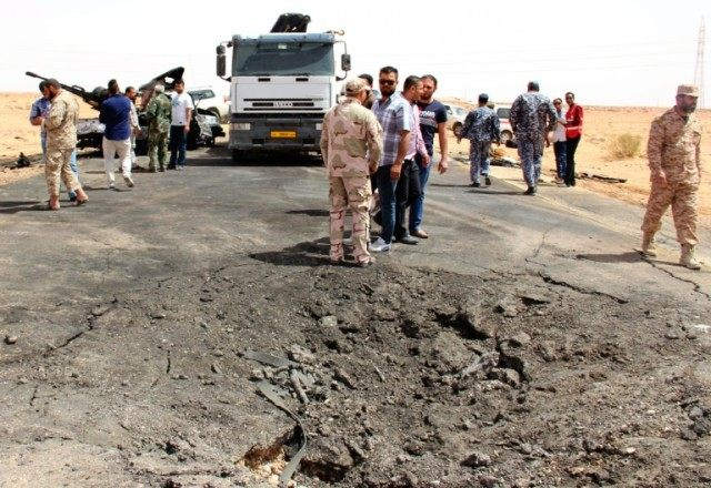 Libyan security forces and citizens look at the damamge following a car bomb attack on a security post in the Saddada area near the eastern Libyan city of Misrata on April 13, 2016