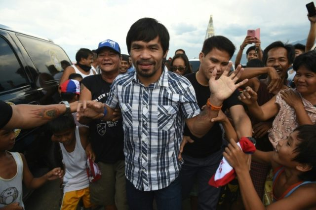 Philippine boxing icon Manny Pacquiao is mobbed by supporters during a visit to Calamba, Laguna province, on April 28, 2016