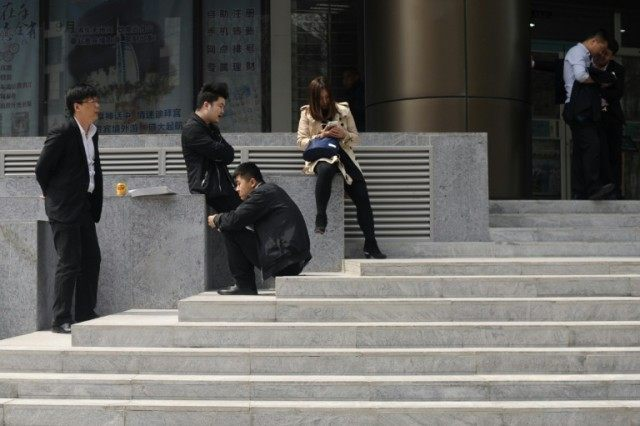 People rest on the steps in front of a bank in Beijing on April 13, 2016