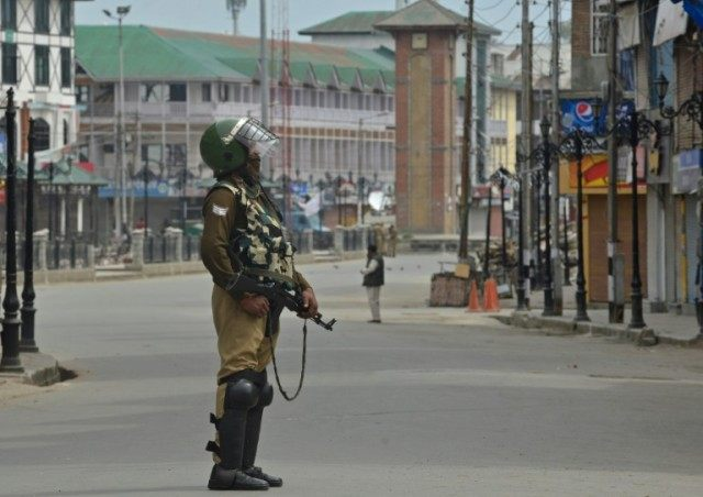 An Indian paramilitary trooper stands guard during a tense curfew in Srinagar on April 15, 2016