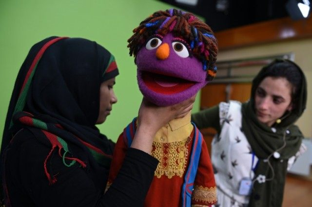 Afghan puppeteer Seema Sultani (R) and her colleague Raziya Nazari work with a muppet named Zari for a recording at a television studio in Kabul