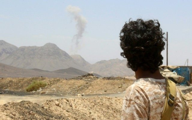 A Yemeni fighter loyal to exiled President Abedrabbo Mansour Hadi looks at smoke rising in the distance in the Sirwah area, in Marib province, on April 10, 2016