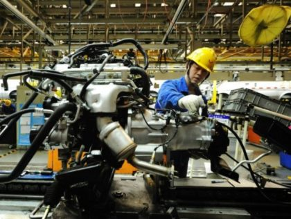 An employee works on an engine at the assembly line of a car factory in Qingdao, eastern China's Shandong province