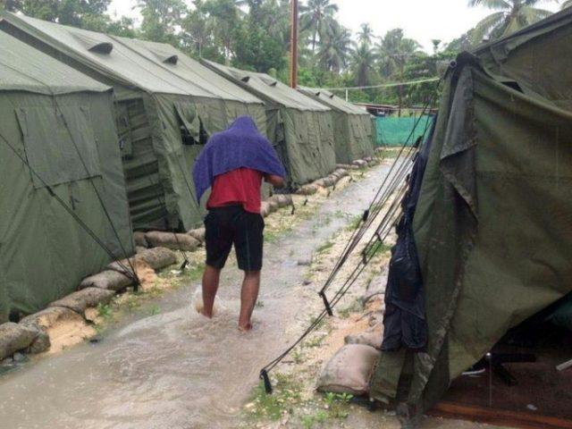 An asylum seeker is seen walking between tents at Australia's processing centre on Manus Island, Papua New Guinea
