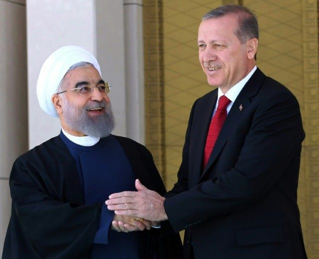 Turkish President Recep Tayyip Erdogan (R) shakes hands with his Iranian counterpart Hassan Rouhani during an official welcoming ceremony at the presidential complex in Ankara on April 16, 2016