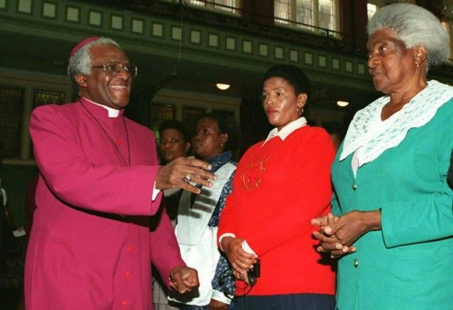 South Africa's Archbishop Desmond Tutu (L) greets witnesses at the start of the second day of the Truth and Reconciliation Commission in the East London