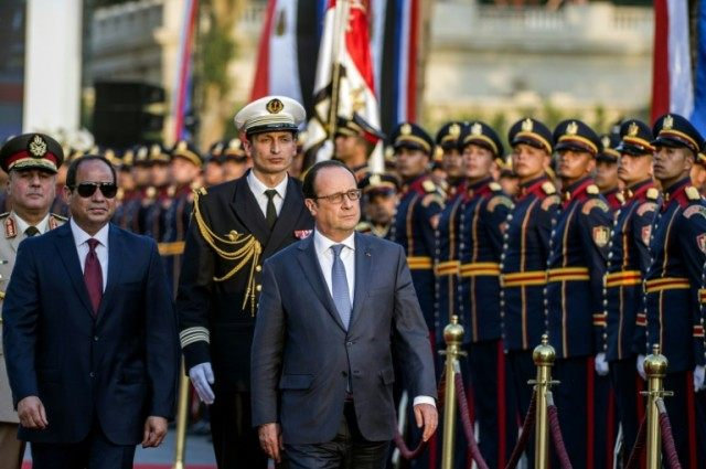 Egyptian President Abdelfattah al-Sisi and his French counterpart Francois Hollande review the honour guard during a welcome ceremony at the al-Quba presidential palace in Cairo on April 17, 2016