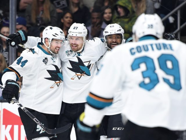 Joonas Donskoi (C) of the San Jose Sharks celebrates his goal with teammates Marc-Edouard Vlasic (L) and Joel Ward during their NHL matcg against the Los Angeles Kings, at Staples Center in Los Angeles, California, on April 22, 2016