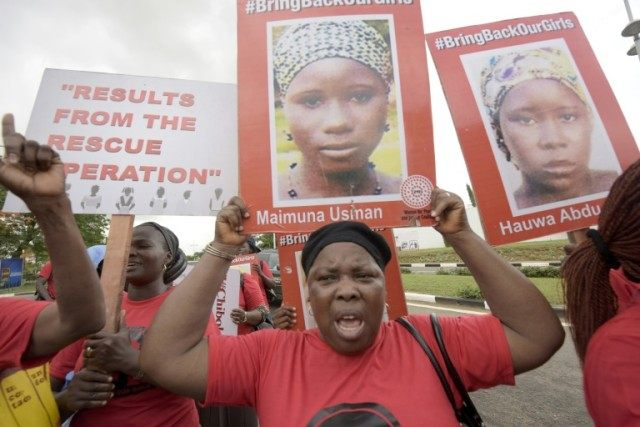"Members of the ""Bring Back Our Girls"" movement carry signs with pictures to press for the release of the missing Chibok schoolgirls, in Lagos on April 14, 2016"
