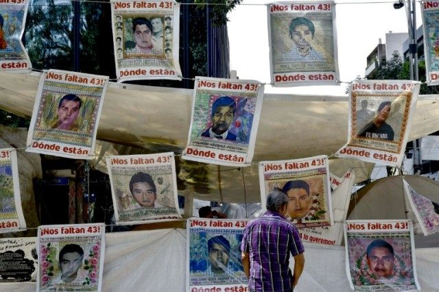 A pedestrian looks at placards with portraits of some of the 43 missing students from the Ayotzinapa teachers' school placed in front of the General Prosecutor of the Republic (PGR) building in Mexico City on April 14, 2016