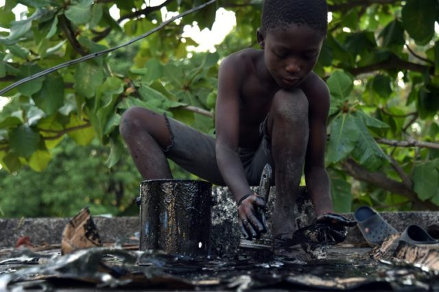 Samuel, 7, varnishes ornaments at the village of Noailles, in Croix des Bouquets, north-east of the capital of Haiti Port-au-Prince