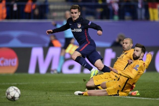 Atletico Madrid's Antoine Griezmann (L) fights for the ball with Barcelona's Javier Mascherano (C) and Gerard Pique during their UEFA Champions League quarter-final 2nd leg match, at the Vicente Calderon stadium in Madrid, on April 13, 2016