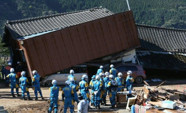 Rescue workers try to save people from a collaspsed house in Mimami-Aso, Kuammoto prefecture, on April 16, 2016 after a powerful earthquake hit southern Japan