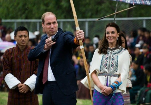 Prince William, Duke of Cambridge, fires an arrow as Catherine, the Duchess of Cambridge, looks on at the Changlingmethang National Archery ground in Thimphu during their visit to Bhutan on April 14, 2016