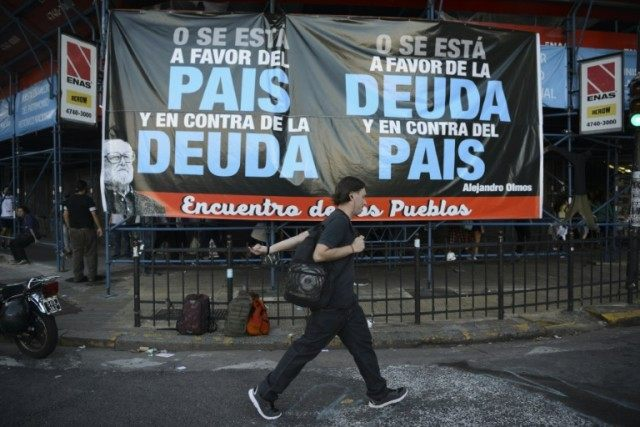 A man walks past a banner calling to reject a deal to repay disgruntled creditors, while the Argentinian government worked to end a 15-year battle in the US courts over a catastrophic debt default on March 30, 2016