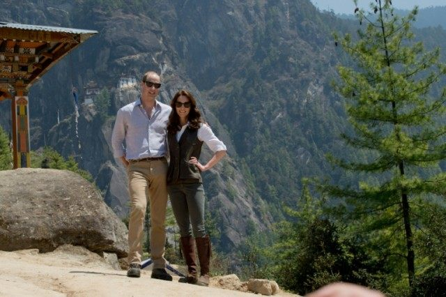 "Britain's Prince William, Duke of Cambridge, and Catherine, Duchess of Cambridge, pose for a photograph halfway up the trail leading to a Buddhist monastery referred to as the ""Tiger's Nest"" (behind) on their two-day visit to Bhutan on April 15, 2016"