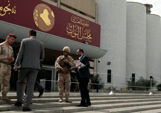 Iraqi security forces stand guard outside the parliament in Baghdad on April 13, 2016