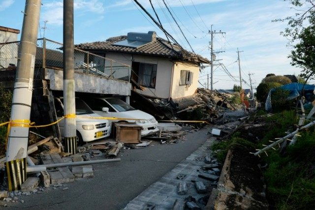 Collapsed houses and damaged cars are seen in Mashiki, Kumamoto prefecture on April 16, 2016 after a powerful earthquake hit southern Japan