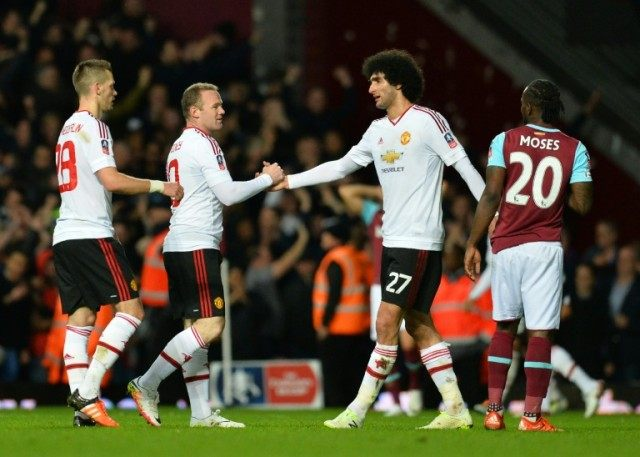 Manchester United's striker Wayne Rooney (2ndL) congratulates midfielder Marouane Fellaini (C) after winning the FA cup quarter final replay on April 13, 2016