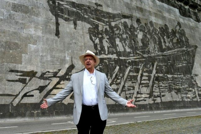 "South African artist William Kentridge poses in front of his mural ""Triumphs and Laments"" on April 13, 2016 in Rome"