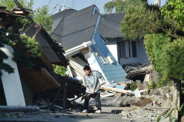 A man clears away the debris of a broken wall in Mashiki, Kumamoto prefecture on April 16, 2016 after a powerful earthquake hit southern Japan