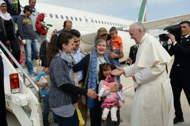 Pope Francis welcomes a group of Syrian refugees after landing at Ciampino airport in Rome following a visit at the Moria refugee camp on April 16, 2016 in the Greek island of Lesbos