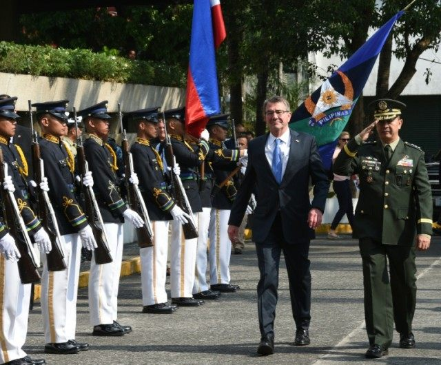 US Defense Secretary Ashton Carter (L) accompanied by Philipine vice-chief of staff Lieutenant General Glorioso Miranda (R) review an honour guard at Camp Aguinaldo in Quezon city, on April 15, 2016
