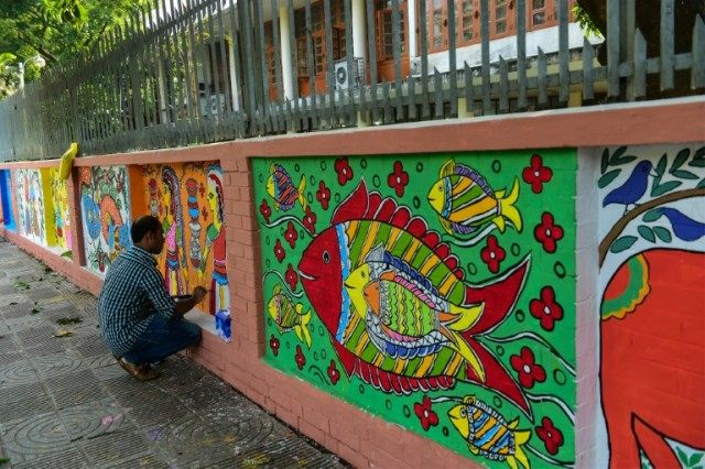 A Bangladeshi Dhaka University Art Institute student paints a mural as a part of Bengali New Year preparations in Dhaka on April 11, 2016