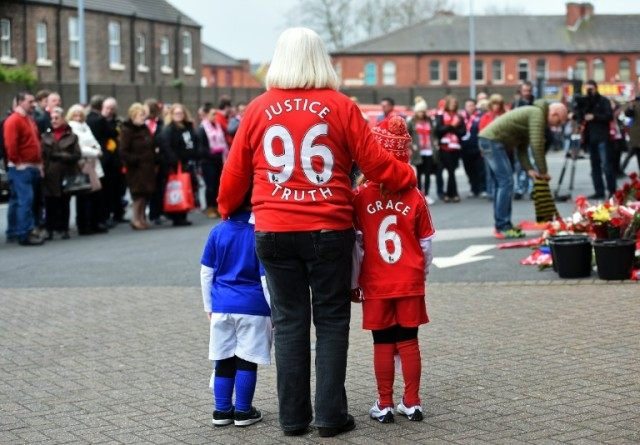 People pay their respects at the temporary Hillsborough memorial, ahead of a service at Anfield in Liverpool on April 15, 2016