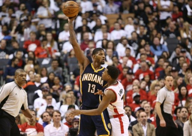 Paul George of the Indiana Pacers keeps the ball out of the reach of Kyle Lowry of the Toronto Raptors in Game One of the NBA Eastern Conference quarterfinals on April 16, 2016 in Toronto