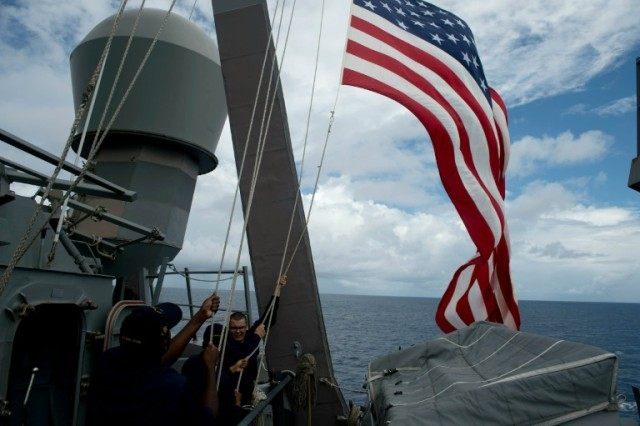 US Navy personnel raise their flag during a bilateral maritime exercise with the Philippine Navy in the South China Sea in 2014