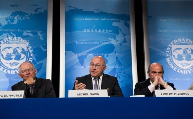 French Finance Minister Michel Sapin speaks next to German Finance Minister Wolfgang Schauble (L) and Spanish Minister of Economy Luis De Guindos (R), during a press conference on April 14, 2016 in Washington, DC