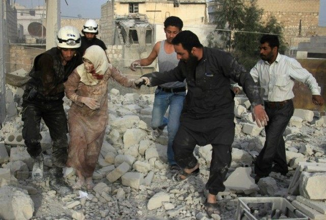 Syrian rescue workers and residents help an injured woman following a reported air strike by government forces on the rebel-held neighbourhood of Haydariya in Aleppo on April 10, 2016
