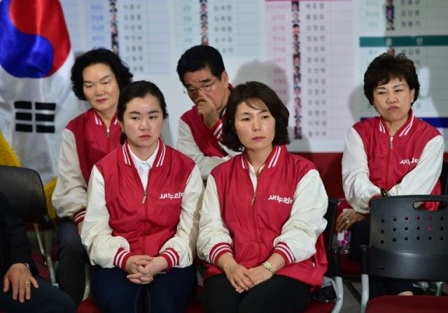 Members of South Korea's ruling Saenuri Party react as they watch a live TV broadcast reporting the results of parliamentary elections at the party headquarters in Seoul on April 13, 2016