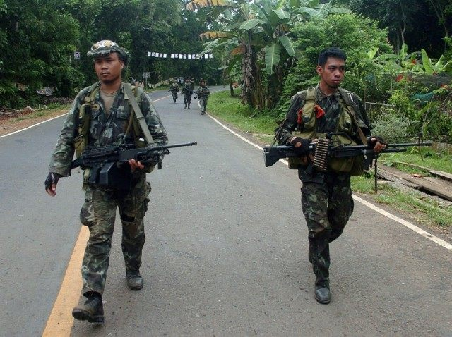 Philippine marines patrol a highway along the village of Busay in Isabela City, Basilan island in the Philippine's southern island of Mindanao as they continue their hunt for Abu Sayyaf militants