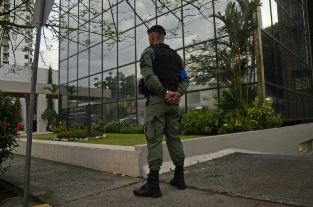 A policeman stands guard outside the Mossack-Fonseca law firm offices in Panama City during a raid on April 12, 2016