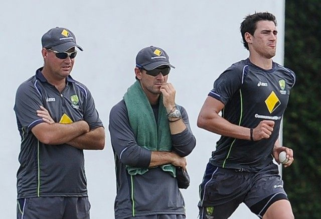 Australian cricketer Mitchell Starc (R) delivers a ball as coach Mickey Arthur (L) and batting coach Justin Langer look on, during an ICC Twenty20 Cricket World Cup practice session in Colombo, in 2012
