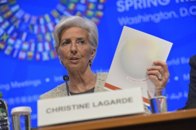 IMF Managing Director Christine Lagarde speaks, holding a copy of the global policy agenda, during the 2016 International Monetary Fund, World Bank Spring Meetings at IMF headquarters on April 14, 2016