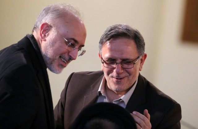 Iran's head of Atomic Energy Organisation Ali Akbar Salehi (L) talks with the Head of the Central Bank of Iran, Valiollah Seif, as they arrive for a press conference of Iranian President on January 17, 2016