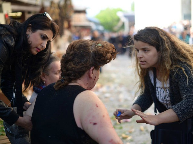 "TURKEY, Bursa : A woman gives first aid to an injured woman following a bombing, in Bursa, northwestern Turkey, on April 27, 2016. A female suicide bomber blew herself up in Bursa on April 27, wounding at least 10 people in the latest attack to strike the country, local media reported. Security sources confirmed that the blast was a ""suicide attack"", while Turkish media identified the bomber as a 25-year-old woman. Nobody has yet claimed responsibility for the blast. / AFP PHOTO / ONUR YURTSEVER"
