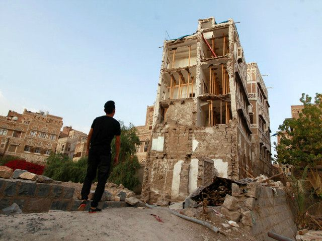 YEMEN, SANAA : A Yemeni man stands on March 23, 2016 in front of UNESCO-listed buildings that was damaged by air strikes carried out by the Saudi-led coalition over the past year in the Yemeni capital Sanaa. Yemen's warring parties have agreed on a ceasefire from April 10 followed by peace talks, a UN envoy said, raising hopes of a breakthrough in a conflict that has devastated the country. / AFP / MOHAMMED HUWAIS