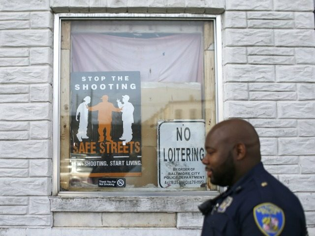 In this March 31, 2016 photo, Baltimore Police Department Officer Jordan Distance walks past signs in a row home's window during a foot patrol in Baltimore. In the year since Freddie Gray died, the Baltimore police department has worked on its relationship with the community and tried to heal wounds …