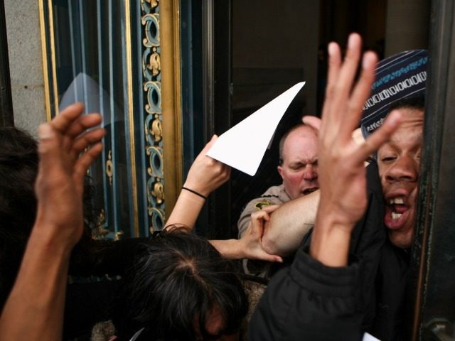 James Burch gets slammed by a San Francisco deputy sheriff, after protestors stormed through the east side entrance of City Hall on Friday, May 6, 2016. Protesters entered the building after doors were locked blocking off the public from entering the building during a protest against SFPD and in support …