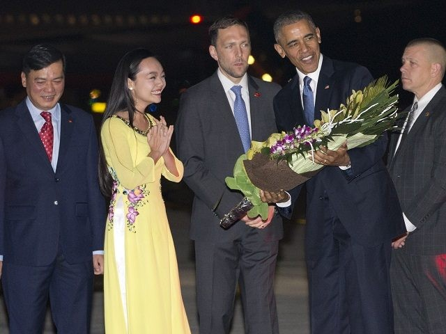 U.S. President Barack Obama is given flowers by Linh Tran, the ceremonial flower girl, as he arrives on Air Force One at Noi Bai International Airport in Hanoi, Vietnam, Sunday, May 22, 2016. The president is on a weeklong trip to Asia as part of his effort to pay more …