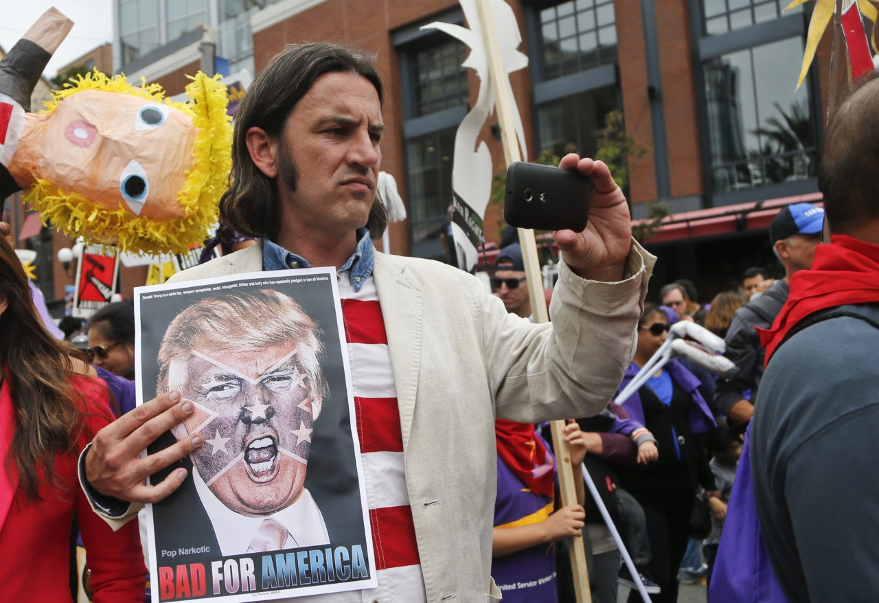 An anti-Trump demonstrator marches outside the San Diego Convention Center where Republican presidential candidate Donald Trump was scheduled to speak, Friday, May 27, 2016, in San Diego. (AP Photo/Lenny Ignelzi)