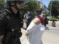 Police officers take a woman into custody after a Republican presidential candidate Donald Trump campaing rally in Fresno, Calif., on Friday, May 27, 2016. Police officers told hundreds of protesters to clear the streets in downtown Fresno following the Trump rally. Officers dressed in riot gear arrested two people on suspicion of unlawfully assembly after they refused orders. (AP Photo/Scott Smith)