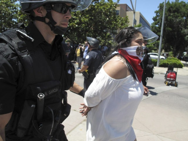Police officers take a woman into custody after a Republican presidential candidate Donald Trump campaing rally in Fresno, Calif., on Friday, May 27, 2016. Police officers told hundreds of protesters to clear the streets in downtown Fresno following the Trump rally. Officers dressed in riot gear arrested two people on …