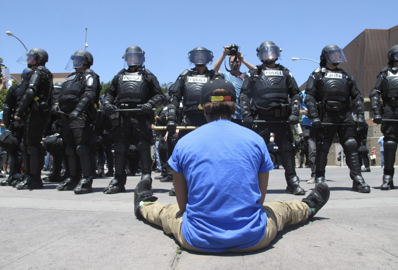 A woman sitting in the street talks with riot police after a campaign rally for Republican presidential candidate Donald Trump in Fresno, Calif., on Friday, May 27, 2016. The crowd beat drums, chanted anti-Trump slogans and marched around the arena in downtown Fresno. Officers arrested two other people after the rally on suspicion of unlawful assembly after they did not follow orders to clear the streets. (AP Photo/Scott Smith)