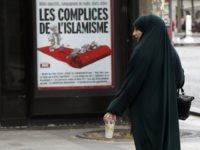 "A muslim woman walks by a ad poster for French magazine Marianne reading ""Radical Islam Accomplice"", during a presentation of security measures at Champs Elysees avenue in Paris, France, Thursday, May 21, 2015. (AP Photo/Francois Mori)"